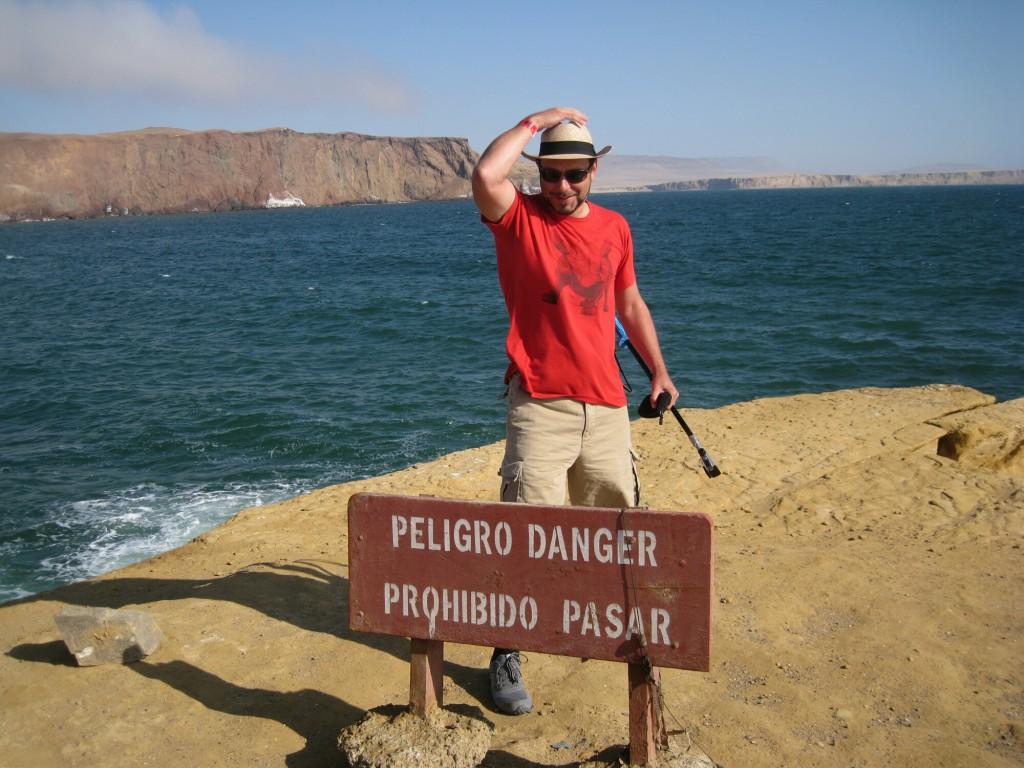Auf dem Schild steht, dass es gefährlich ist wenn man seinen Hut nicht festhält.